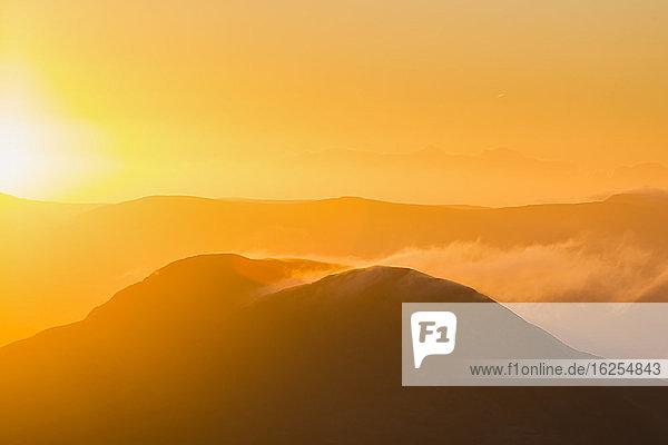Silhouette eines Hügels in Kerry bei Sonnenaufgang mit Schneeverwehungen von der Spitze  MacGillycuddy's Reeks; Grafschaft Kerry  Irland