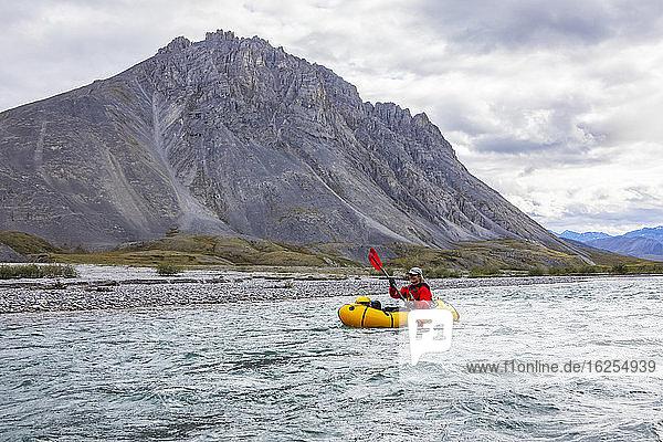 Kaukasische Frau im roten Trockenanzug paddelt an einem bewölkten Sommertag mit ihrem gelben Packboot den Marsh Fork-Fluss hinunter  mit großen Bergen im Hintergrund  Brooks Range  Arctic National Wildlife Refuge; Alaska  Vereinigte Staaten von Amerika