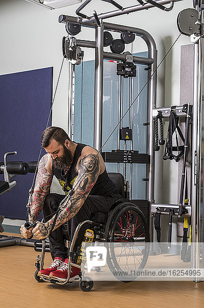 A paraplegic man working out using a crossover pulley weight lifting apparatus in a fitness facility; Sherwood Park  Alberta  Canada
