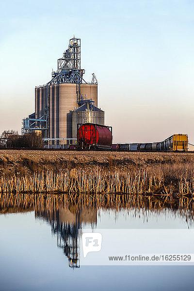 Getreidespeicher und Zug in den Prärien von Alberta im Wasser reflektiert; Alberta  Kanada