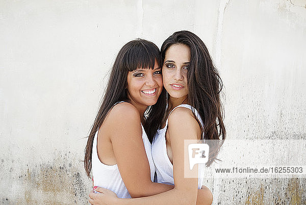 Portrait of two beautiful young women with long brown hair  hugging and smiling at camera.
