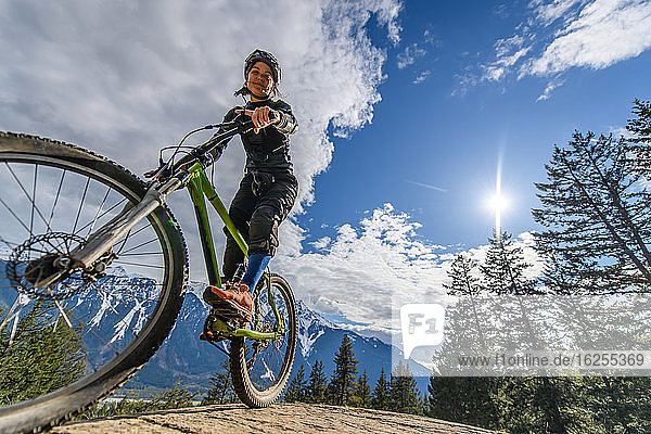 Woman mountain-biking in a forest in the Canadian mountains