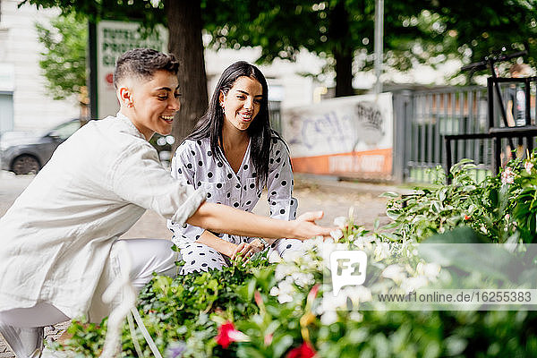 Young lesbian couple standing at market stall  looking at plants.