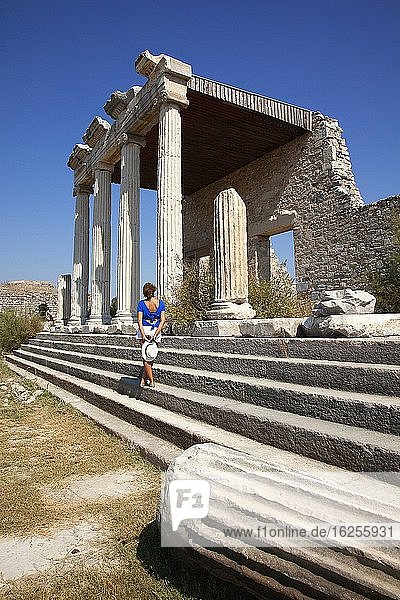 Tourist woman standing in front of Ionic Stoa-stone temple in the ancient ruins of Miletus  Miletos  Milet  Aydin Province  Turkey  Europe