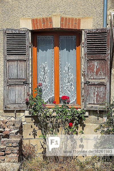 Window with old grey shutters in France