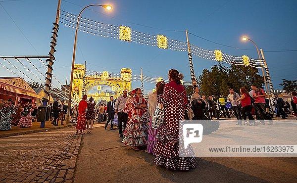 Spanish women with flamenco dresses in front of the illuminated Portada  entrance gate  Feria de Abril  Sevilla  Andalusia  Spain  Europe
