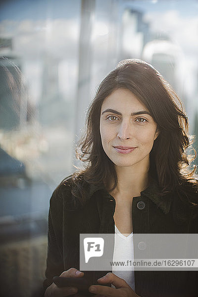 Porträt einer selbstbewussten Geschäftsfrau  die mit einem Smartphone am Fenster simst