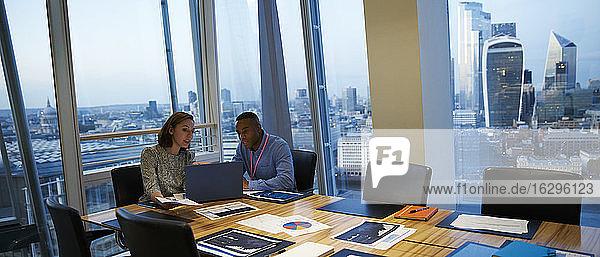Geschäftsleute arbeiten am Laptop in einem Hochhaus-Konferenzraum