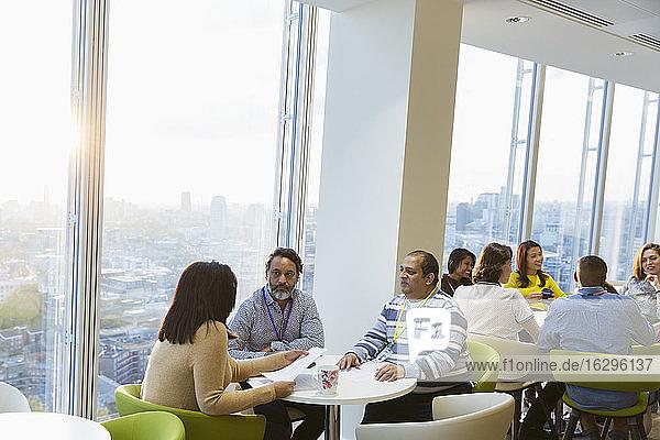 Geschäftsleute treffen sich in sonniger Hochhaus-Bürocafeteria