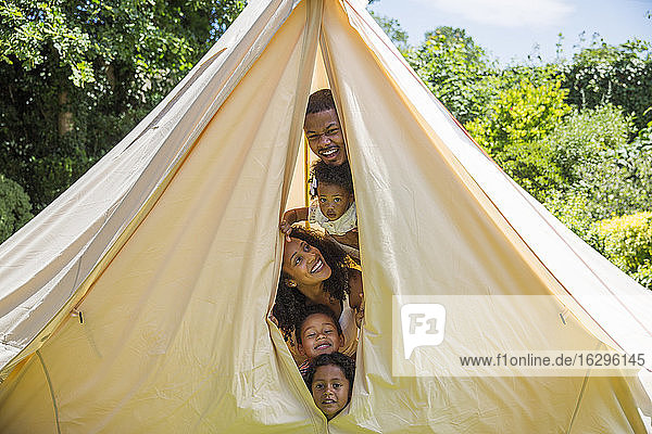 Porträt einer spielerischen Familie  die aus dem Innenzelt schaut