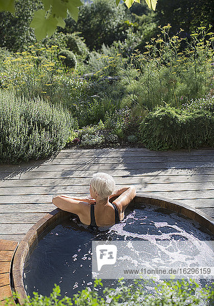 Senior woman relaxing in hot tub on sunny summer patio