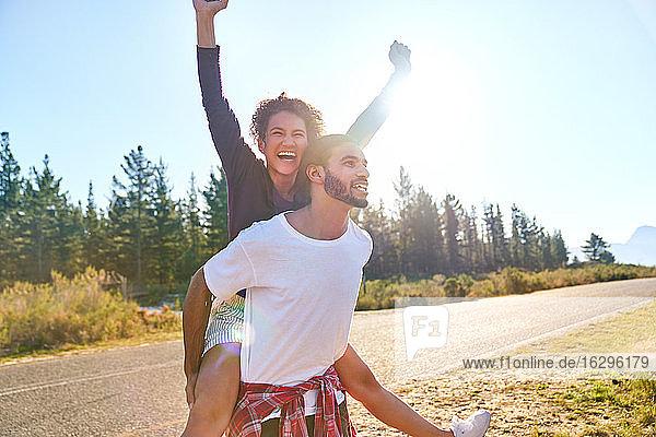 Porträt eines sorglosen jungen Paares beim Huckepackfahren an einem sonnigen  abgelegenen Straßenrand