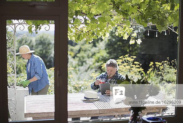 Älteres Ehepaar gärtnert und benutzt digitales Tablet auf sonniger Sommerterrasse