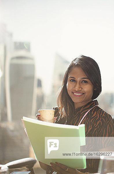 Porträt einer glücklichen Geschäftsfrau mit Papierkram am sonnigen Bürofenster