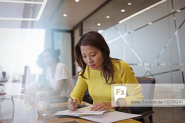 Geschäftsfrau mit Papierkram im Konferenzraum