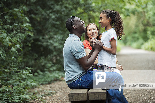 Glückliche Familie auf der Parkbank