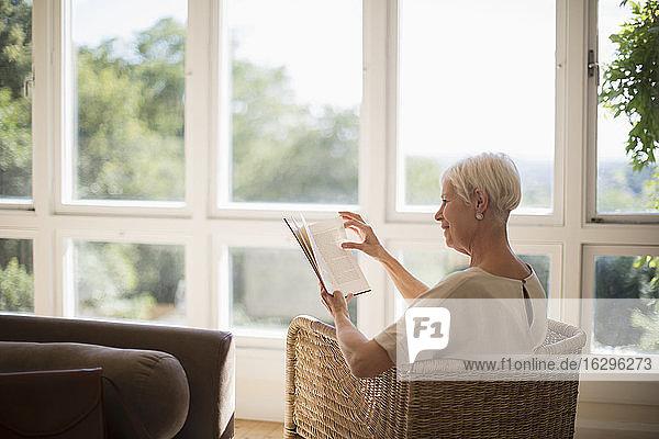 Ältere Frau entspannt sich und liest ein Buch im sonnigen Wohnzimmer