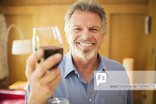 Porträt eines glücklichen  sorglosen älteren Mannes  der Rotwein trinkt