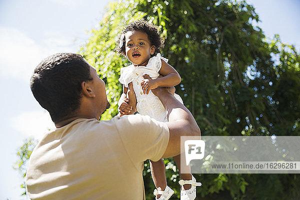 Vater hebt Kleinkind-Tochter über Kopf in sonnigen Sommerhof