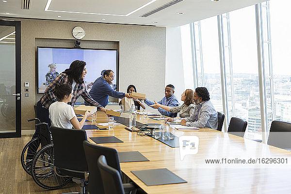 Geschäftsleute bringen Mitarbeitern im Konferenzraum das Mittagessen