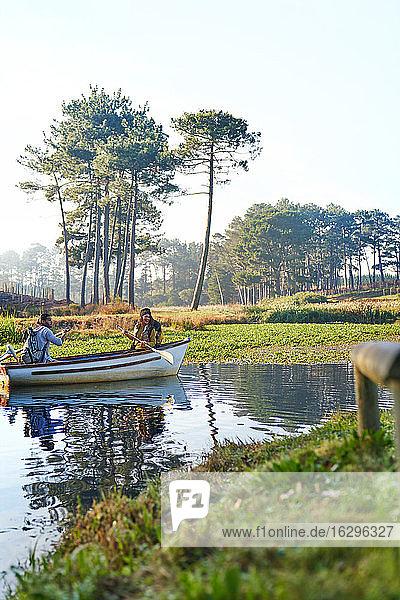 Junges Paar im Ruderboot auf einem sonnigen  ruhigen Teich