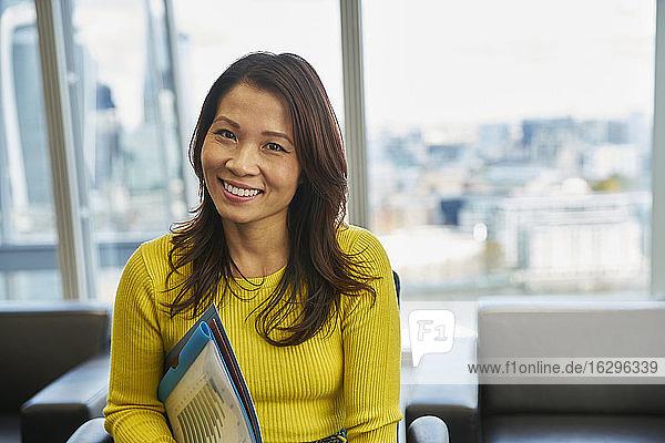 Porträt einer lächelnden Geschäftsfrau mit Papierkram im Büro