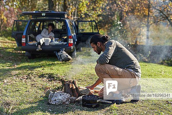 Mann bereitet Lagerfeuer vor dem Auto im sonnigen Herbstfeld