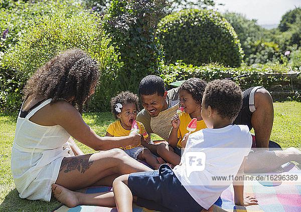 Glückliche Familie isst Wassermelonen-Eis am sonnigen Sommerhinterhof