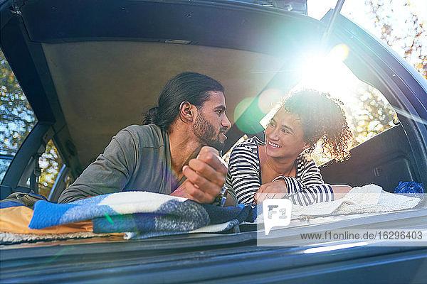 Glückliches junges Paar entspannt sich auf dem Rücksitz eines sonnigen Autos