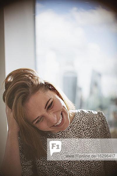 Glückliche Geschäftsfrau  die mit der Hand im Haar am Fenster lacht