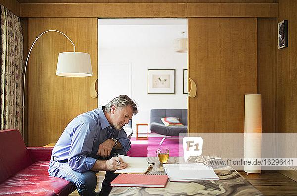 Älterer Mann mit Notebook bei der Arbeit im Wohnzimmer