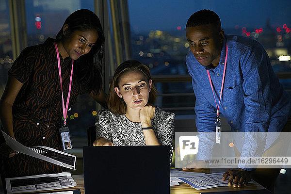Geschäftsleute  die spät am Laptop im Büro arbeiten