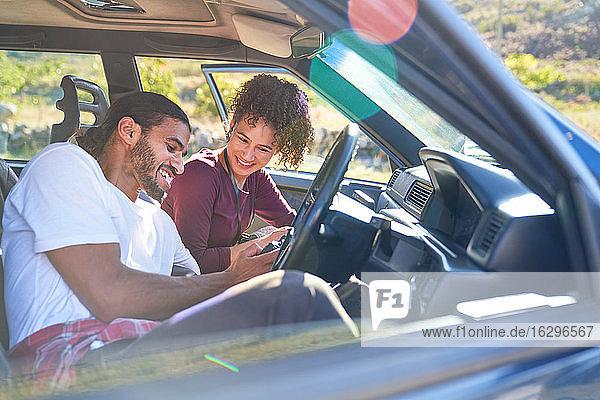 Glückliches junges Paar genießt Autoreise im sonnigen Auto