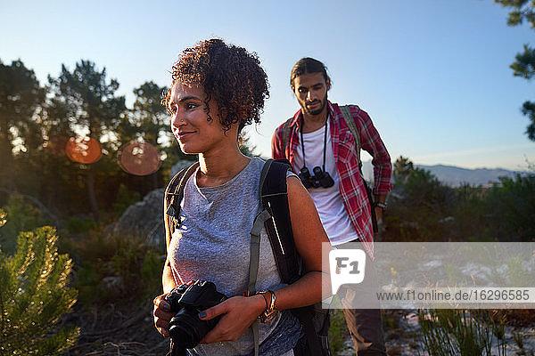 Junges Paar wandert mit Kamera und Fernglas in sonniger Natur