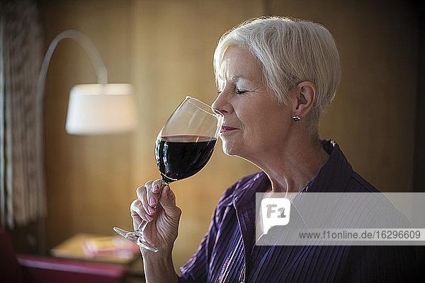 Gelassene ältere Frau  die Rotwein riecht und schmeckt