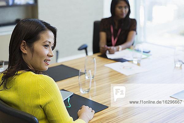 Lächelnde Geschäftsfrau beim Zuhören im Konferenzraum