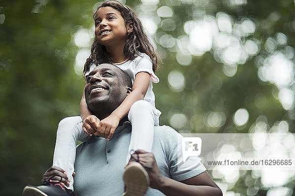 Happy father carrying daughter on shoulders