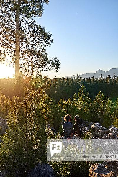 Junges Wandererpaar geniesst bei Sonnenuntergang sonnige Aussicht auf Bäume im Wald