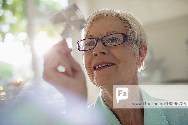 Neugierige ältere Frau untersucht Würfel im Sonnenlicht