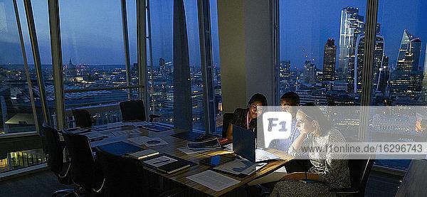 Geschäftsleute  die spät am Laptop im Hochhausbüro arbeiten  London  UK