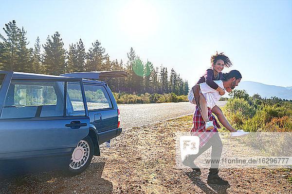 Unbeschwertes junges Paar beim Huckepackfahren im Auto am sonnigen Straßenrand