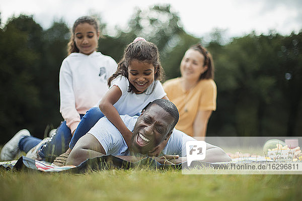 Fröhlich-verspielte Familie auf Picknickdecke im Park