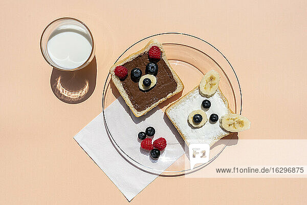 Studio shot of glass of milk and toasts with bear faces made of fruits
