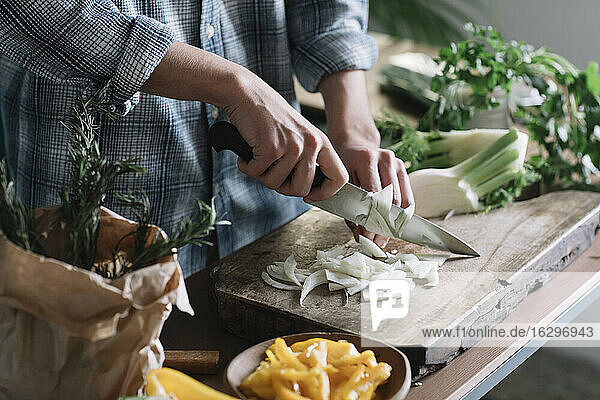 Midsection of young man cutting fennel on board in kitchen