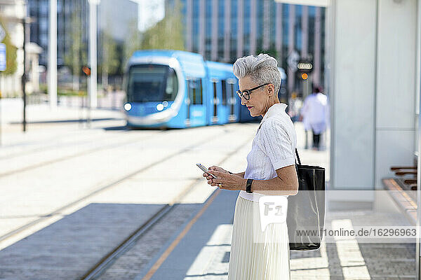 Senior woman text messaging on smart phone while standing in city at tram stop
