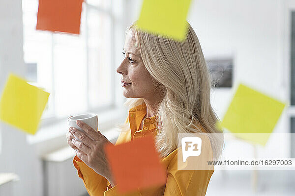 Thoughtful businesswoman holding coffee cup in home office seen through window
