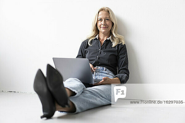 Smiling businesswoman using laptop while sitting on floor against wall in office