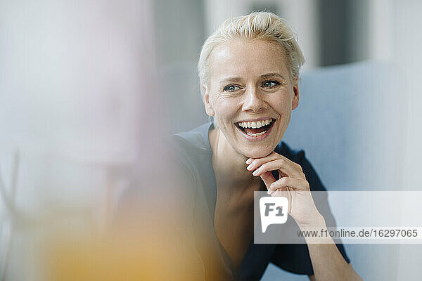 Close-up of businesswoman with hand on chin laughing while sitting in office