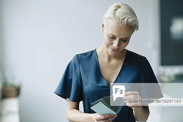 Close-up of businesswoman choosing color swatch while standing against wall in office