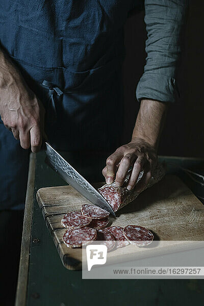 Midsection of man cutting salami slices on board at table